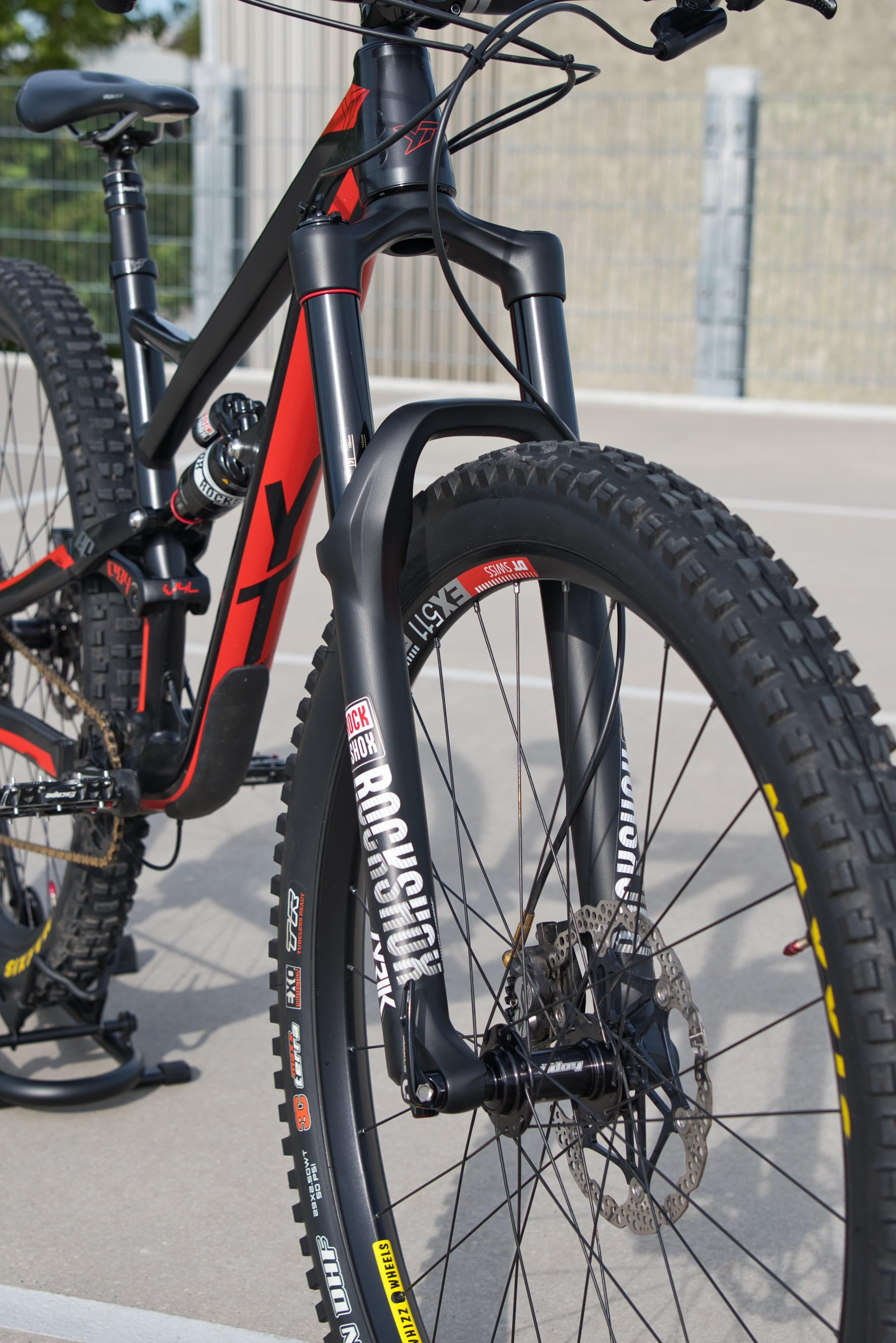 Red Mountainbike Detailed Shot. Front Rockshox Lyrik Fork with Debonaire Upgrade installed